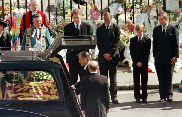FILE PHOTO: Earl Spencer, Prince William, Prince Harry and Prince Charles watch as the coffin of Diana, Princess of Wales is placed into a hearse at Westminster Abbey following her funeral service